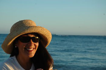 A woman on the beach in a hat and glasses smiling because of the dental implants she received from her dentist in Columbia SC