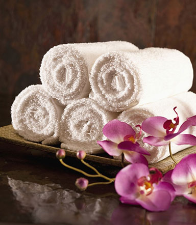 Warm towels rolled and stacked in a wood tray next to pink flower blossoms to illustrate the relaxing effect of sedation dentistry