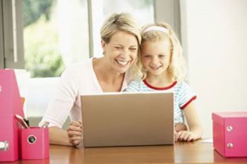 An older woman and a young girl looking a a laptop and learning facts about dentistry