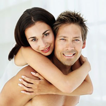 A woman with her arms wrapped around her boyfriend with bright white smiles due to professional teeth whitening in Columbia, SC