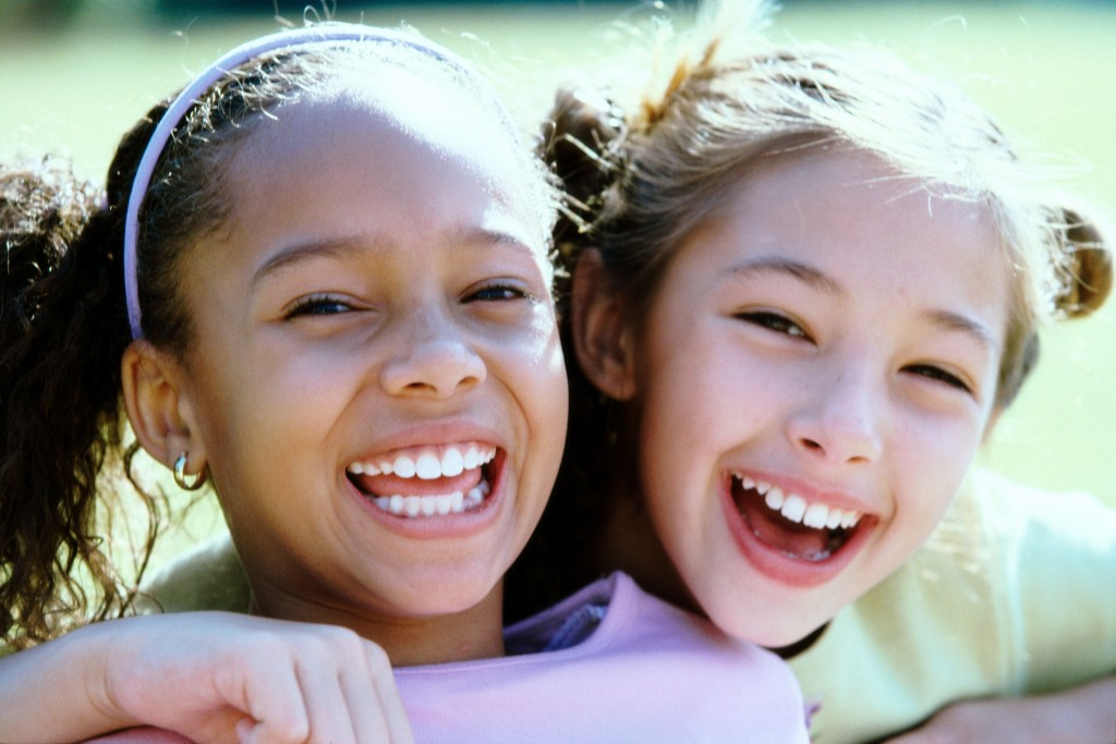 Two young girls hugiing playfully with growing smiles to show that vitamin d can help with cavities