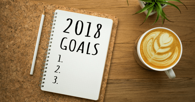 """A notebook with the words """"2018 Goals"""" written on it next to a pencil and a warm latte to remind us to stick to our new years resolution goals"""