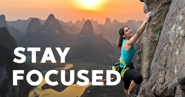 """A woman scaling the face of a mountain with the sun rising in the background with the words """"STAY FOCUSED"""" to remind us to stay focused on our new years resolutions"""