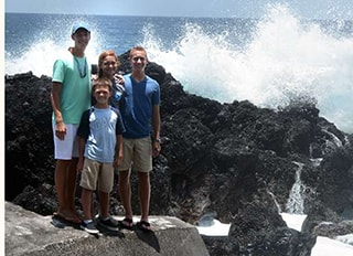Dr. Griffin and his kids standing on rocks at the beach.