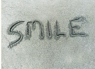 The word smile written in the sand at the beach.
