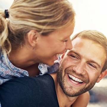 Young couple laughing confidently with bright healthy smiles thanks to Wildewood's Columbia SC dental services
