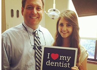 Dr. Griffin and a young patient holding a sign that says I love My Dentist