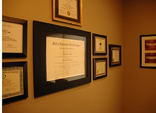 Diplomas and awards on the wall of WildeWood Aesthetic Dentistry
