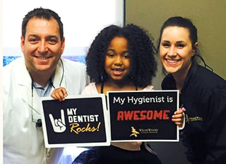 Dr. Griffin, a cosmetic dentist in Columbia, SC and his dental assistant with a young patient.
