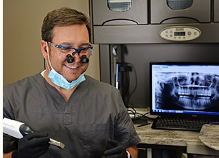 Dr. Griffin giving a treatment with his dental team assisting