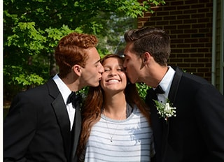 A girl being kissed on the cheeks by two boys