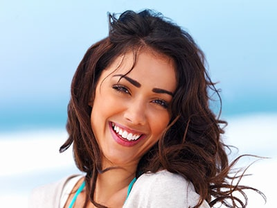 Smiling vibrant young woman asking about porcelain veneers