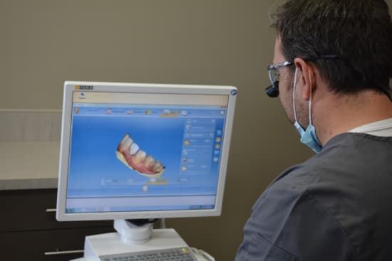 Dr. Griffin sitting in front of a computer reviewing a 3D x-ray in preparation for placing dental implants in Columbia, SC