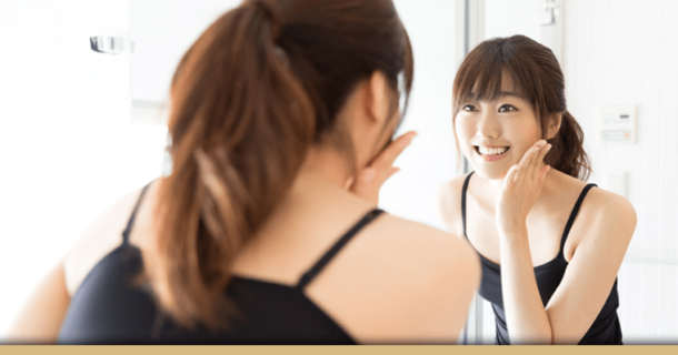 Girl looking at teeth in mirror wondering if prepless veneers are aright for her.
