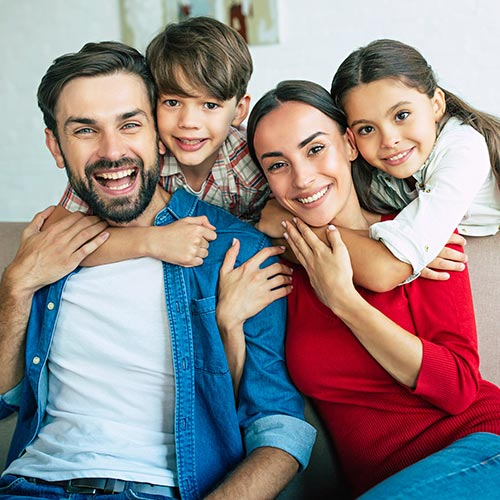 Young family of four smiling and sitting on their couch with healthy smiles from general dentistry.